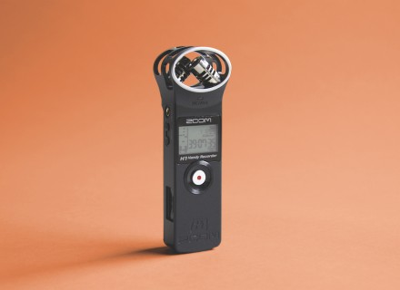 Image of a Zoom H1 black audio recorder standing upright with an orange coloured background