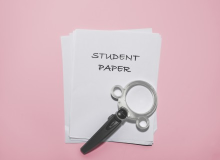 "Image of a magnifying glass laying on a stack of white paper with the top piece of paper showing the text ""student paper"""
