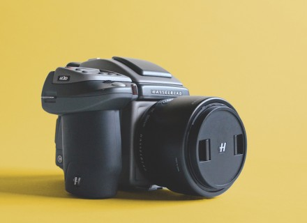 photo of a hasselblad digital camera with lens sitting on yellow backdrop.