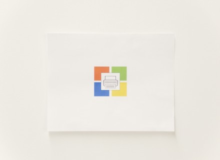 Photo from an overhead angle of a printer piece of paper with a windows icon and a printer icon on it.
